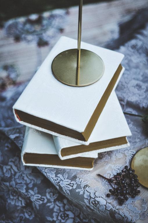 Grāmatas ar gaiša auduma vākiem un zeltītas krāsas malām
